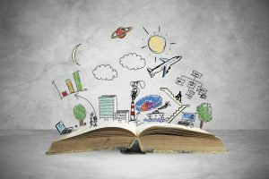 Photo of book splayed open with colorful drawings of trees, and buildings, clouds, an airplane, charts, people, star and sun.  Depicting the many types of ideas that people think of.