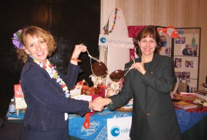 Veronica Adams shaking hands and presenting cocoanut brazzier to smiling woman at business women's conference.