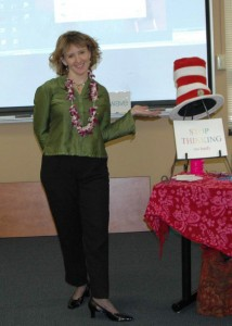 Veronica Adams pointing to a Dr. Seuss hat and a sign that reads