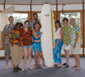 Riding the wave team members with surfboard in beach ware.